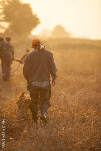 Hunter and his dog walking on field during quail hunt Wall mural