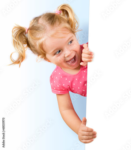 Fotografia Smiling little girl looking behind a white board
