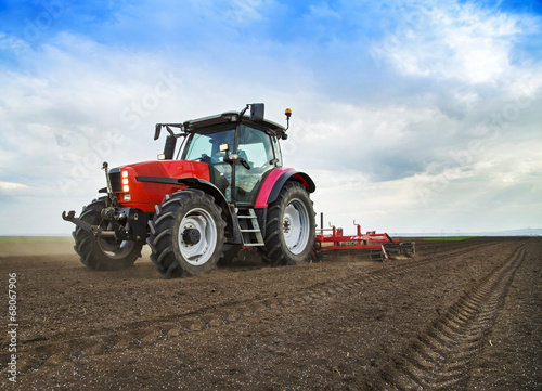 Leinwand Poster  Farmer in tractor preparing land for sowing