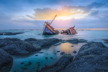 Shipwreck Or Wood Ship Broken Damage On Land, Coast Or Beach With Sea And Sunset Background. That Result Of Accident, Storm, Crash, Wave In Ocean Or Marine. For Assurance, Travel Or Adventure Concept.