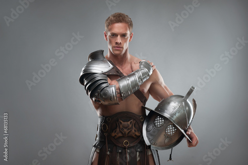 Gladiator in armour posing with helmet over grey background Wallpaper Mural