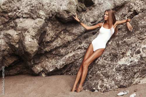 Photo  The young beautiful woman with tan on the beach, near the rocks