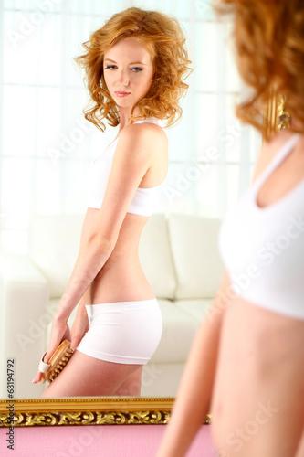 Fototapeta Beautiful young woman massaging her leg near mirror in room obraz na płótnie