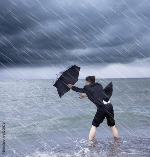 Obraz na płótnie business man holding a umbrella to resist rainstorm