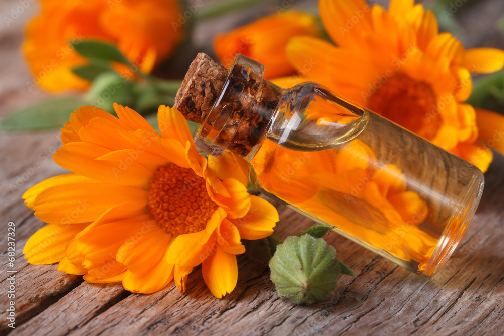 Fototapety, obrazy: Calendula oil in a glass bottle on an old table horizontal