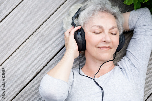 Seniorin mit Kopfhörern genießt Musik Canvas Print