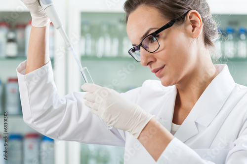 Fotografía  Scientist using pipette in laboratory