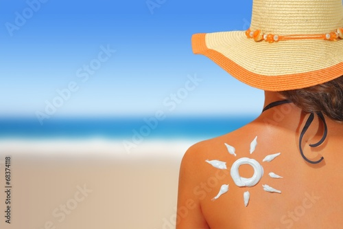 Woman with sun shaped sunscreen on her back Wallpaper Mural