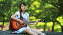 Young Asian Woman Outdoor In Park Playing Guitar Singing