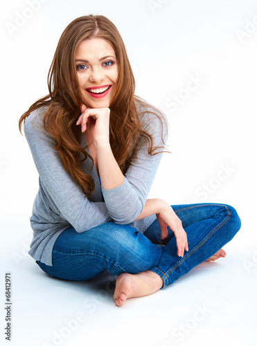 Young woman sitting on a floor. Isolated on white background