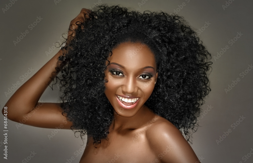 Fototapeta Young woman happy with curly hairstyle on a grey background
