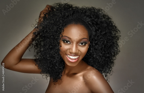 Foto op Plexiglas Kapsalon Young woman happy with curly hairstyle on a grey background