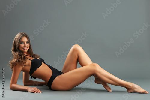 Fototapeta Beautiful woman with slim body in swimsuit on gray background obraz na płótnie