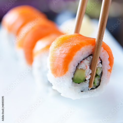 Printed kitchen splashbacks Sushi bar picking up a piece of sushi with chopsticks