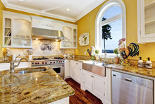Bright Yellow Kitchen Room With Granite Tops And Arch Window
