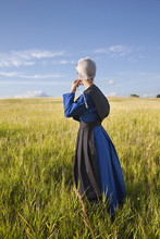 Amish Woman Standing In Grassy...