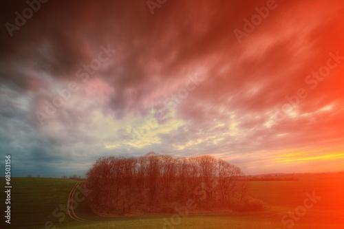 Staande foto Baksteen Zachód słońca nad zielonym polem z chmurami
