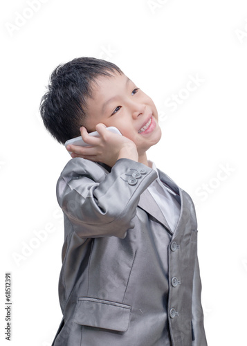 Valokuva  Asian boy in suit talking on mobile phone over white background