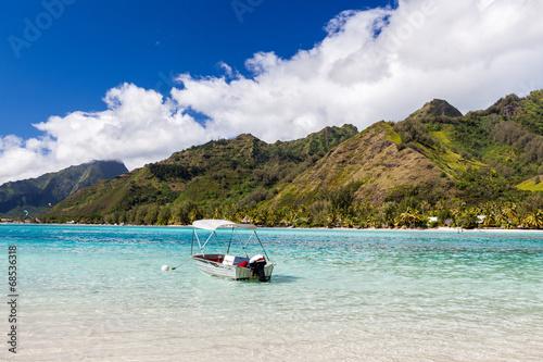 Barca a motore con tendalino ancorata in mare tropicale