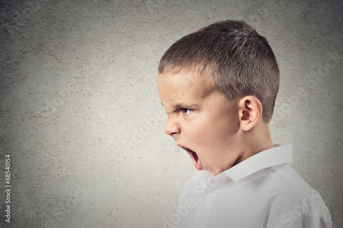 side view profile portrait angry boy screaming grey background