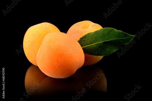Fotografia Three whole apricots with leaf isolated on black