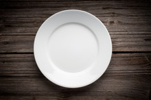 Empty White Plate On Wooden Ta...