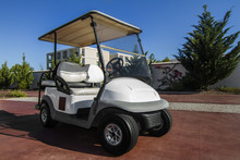 Close Up View Of A White Golf Cart Parked On The Road.
