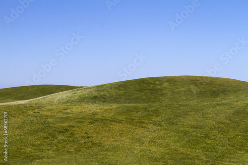 View of bare green hills with a blue sky.