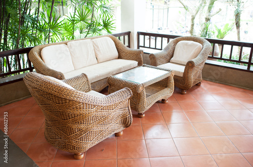 Fotobehang Tuin Home exterior patio with wooden decking and rattan sofa