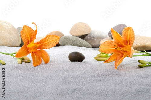 Foto auf Leinwand Zen-Steine in den Sand Pebble stones and orange lily flowers on gray sand