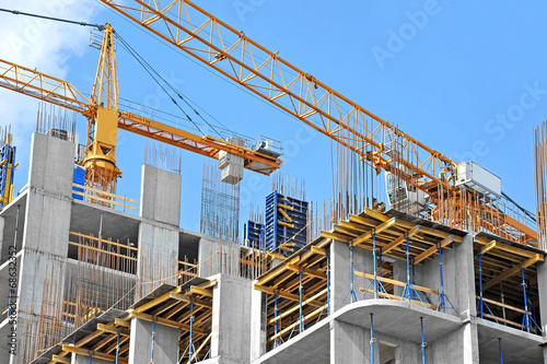 Papel de parede Crane and building construction site against blue sky