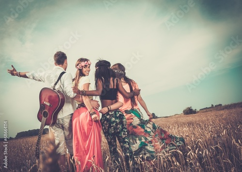 Платно Multi-ethnic hippie friends with guitar in a wheat field