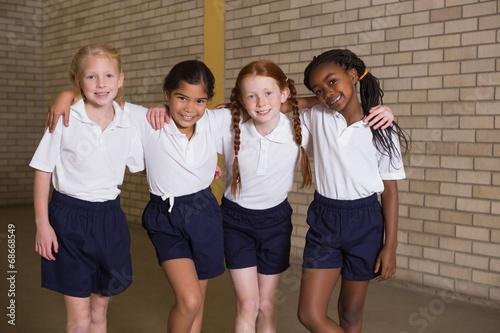 Fotografía  Cute pupils smiling at camera in PE uniform