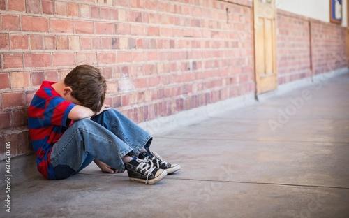Sad pupil sitting alone in corridor Canvas Print