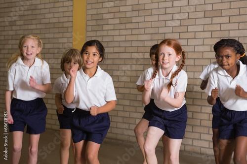 Fotografía  Cute pupils warming up in PE uniform