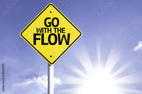 Photo  Go With The Flow road sign with sun background