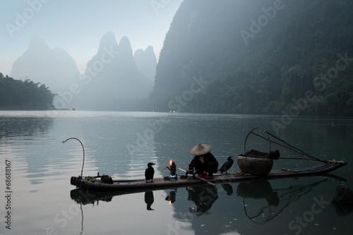 Valokuva YANGSHUO - JUNE 18: Chinese man fishing with cormorants birds in