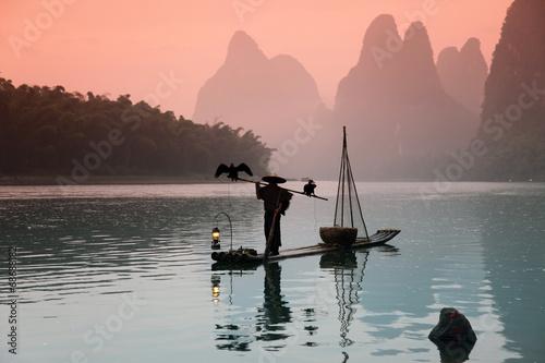 Fotografía YANGSHUO - JUNE 18: Chinese man fishing with cormorants birds in