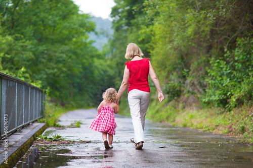 Fotografia, Obraz  Mother and daughter walking in a park