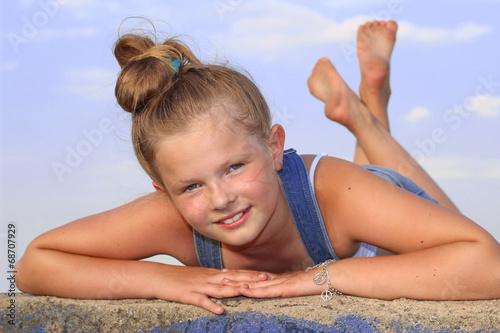 Fotografie, Obraz  Wesoła dziewczynka leżąca na brzuchu na murku