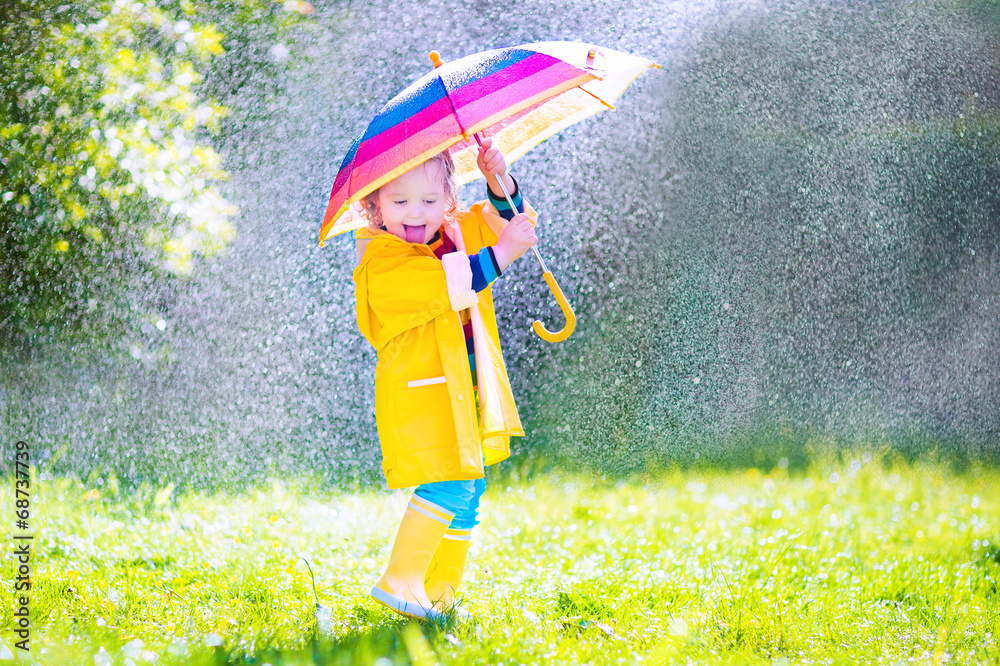 Fototapeta Funny little toddler with umbrella playing in the rain