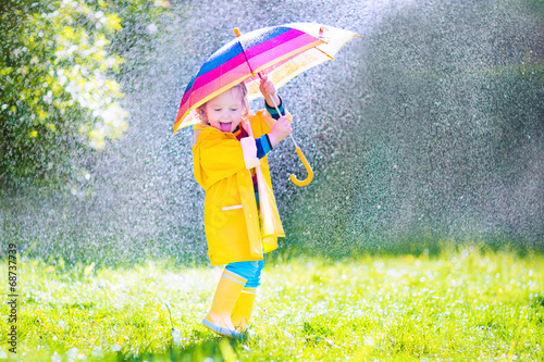 Fotografie, Obraz  Funny little toddler with umbrella playing in the rain