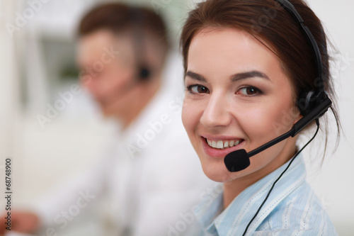 Fotografía  Businesswoman with headset smiling at camera in call center