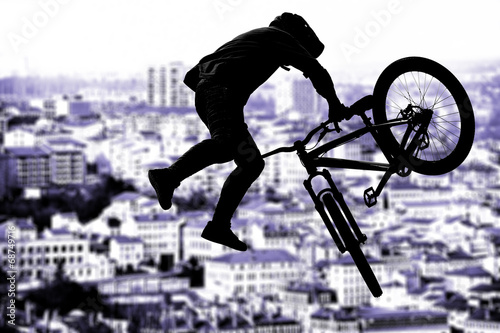 Silhouette bmx sport rider in action with scenery background