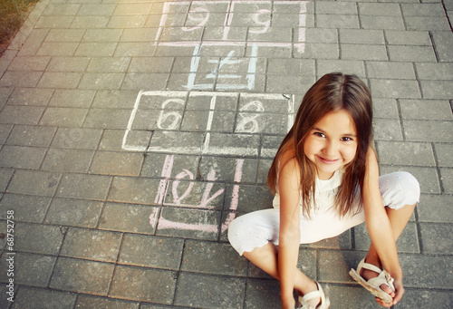 Obraz beautiful cheerful little girl playing hopscotch on playground - fototapety do salonu