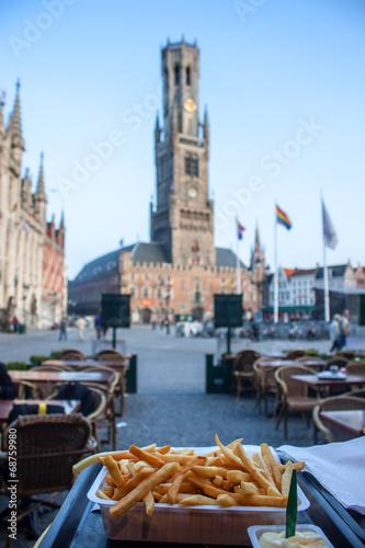 In de dag Brugge Typical belgian meal - frie; Bell Tower in Bruges. Shallow DOF.