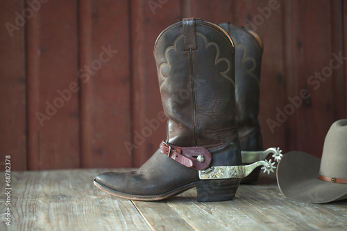 Valokuva  Cowboy boots, spurs and hat on old wood background