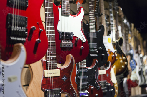 Photo Stands Music store Many electric guitars hanging on wall in the shop.