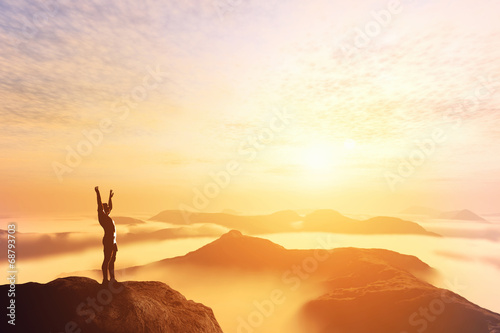 Fotografia Happy man with hands up on the top of the world above clouds