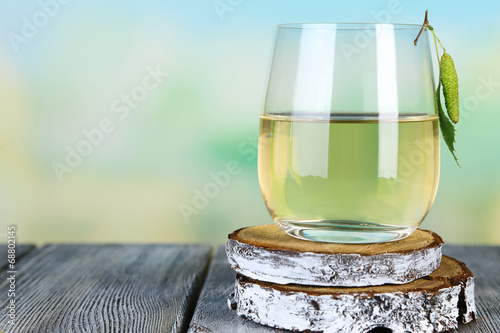 Glass of fresh birch sap on a wooden table on nature